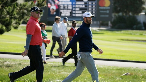Ted Potter Jr., left, and Dustin Johnson, right, walks down the third fairway of the Pebble Beach Golf Links during the final round of the AT&T Pebble Beach National Pro-Am golf tournament Sunday, Feb. 11, 2018, in Pebble Beach, Calif. (AP Photo/Eric Risberg)