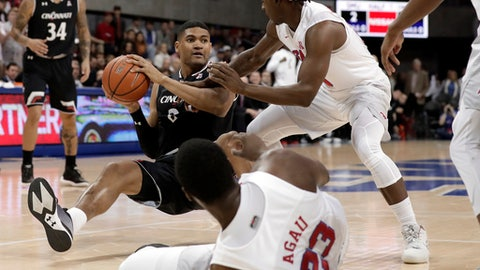 Cincinnati forward Kyle Washington (24) attempts to pass the ball as he falls after colliding with SMU forward Akoy Agau (23) of Sudan as guard Elijah Landrum, right, defends in the first half of an NCAA college basketball game Sunday, Feb. 11, 2018, in Dallas. (AP Photo/Tony Gutierrez)