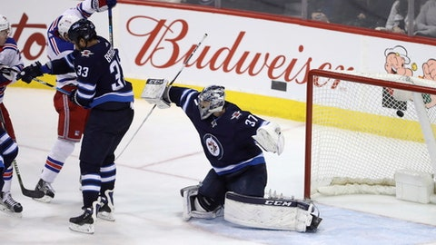 New York Rangers' Jimmy Vesey (not shown) scores on Winnipeg Jets goaltender Connor Hellebuyck (37) during third period NHL hockey action in Winnipeg, Manitoba, Sunday, Feb. 11, 2018. (Trevor Hagan/The Canadian Press via AP)