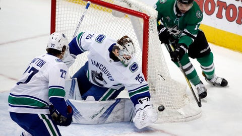 Vancouver Canucks goaltender Jacob Markstrom (25) gets to the puck before Dallas Stars center Devin Shore (17) as Canucks defenseman Ben Hutton (27) defends, during the second period of an NHL hockey game in Dallas, Sunday, Feb. 11, 2018. (AP Photo/Michael Ainsworth)