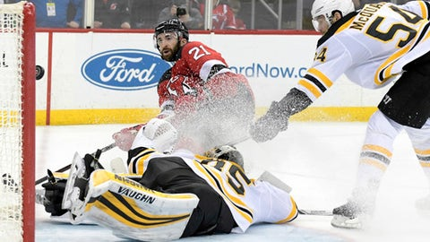 New Jersey Devils right wing Kyle Palmieri (21) scores a goal against Boston Bruins goaltender Anton Khudobin (35) and Bruins defenseman Adam McQuaid (54) during the second period of an NHL hockey game Sunday, Feb. 11, 2018, in Newark, N.J. (AP Photo/Bill Kostroun)