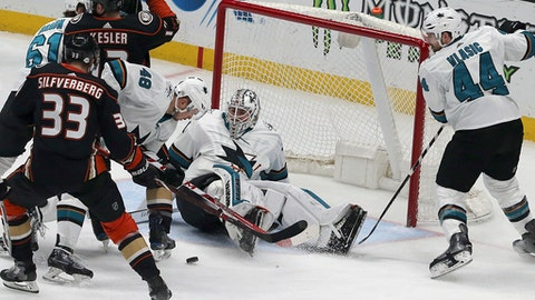 San Jose Sharks goalie Martin Jones (31) and defenseman Marc-Edouard Vlasic (44) defend against Anaheim Ducks right winger Jakob Silfverberg (33) in the first period of an NHL hockey game in Anaheim, Calif., Sunday, Feb. 11, 2018. (AP Photo/Reed Saxon)