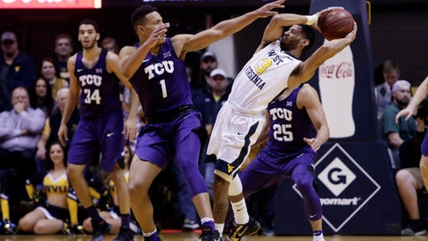 West Virginia guard James Bolden (3) pass the ball while being defended by TCU guard Desmond Bane (1) during the first half of an NCAA college basketball game Monday, Feb. 12, 2018, in Morgantown, W.Va. (AP Photo/Raymond Thompson)
