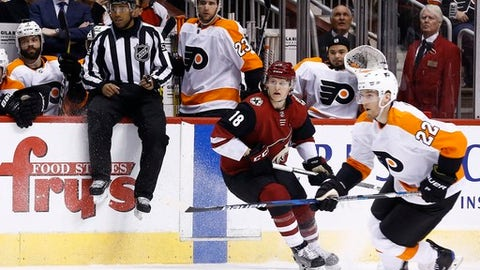 Linesman Shandor Alphonso, second from left, jumps out of the way between Philadelphia Flyers defenseman Radko Gudas, left, and Flyers defenseman Brandon Manning (23) on the team bench as Arizona Coyotes center Christian Dvorak (18) and Flyers right wing Dale Weise (22) watch the movement of the puck during the third period of an NHL hockey game Saturday, Feb. 10, 2018, in Glendale, Ariz.  The NHL has almost two dozen black players but just one black official in linesman Shandor Alphonso and one black coach in Flames assistant Paul Jerrard.  (AP Photo/Ross D. Franklin)