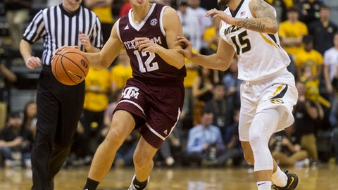 Texas A&M's Chris Collins, left, is defended by Missouri's Jordan Geist, right, as he brings the ball up court during the first half of an NCAA college basketball game Tuesday, Feb. 13, 2018, in Columbia, Mo. (AP Photo/L.G. Patterson)