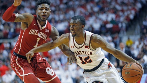 Texas Tech's Keenan Evans (12) lays up the ball around Oklahoma's Christian James (1) during an NCAA college basketball game Tuesday, Feb. 13, 2018, in Lubbock, Texas. (AP Photo/Brad Tollefson)