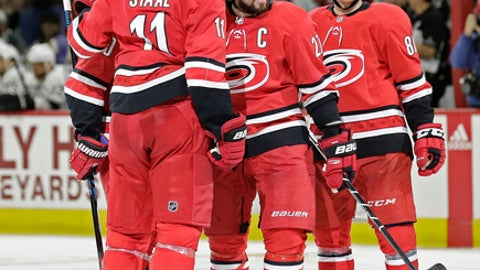 Carolina Hurricanes' Justin Faulk, center, is congratulated by Jordan Staal (11) and Teuvo Teravainen (86), of Finland, following Faulk's hat trick goal against the Los Angeles Kings during the second period of an NHL hockey game in Raleigh, N.C., Tuesday, Feb. 13, 2018. (AP Photo/Gerry Broome)