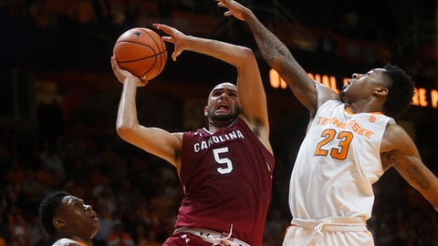 South Carolina guard Frank Booker (5) goes up for a shot between Tennessee forward Admiral Schofield, left, and guard Jordan Bowden (23) during the second half of an NCAA college basketball game Tuesday, Feb. 13, 2018, in Knoxville, Tenn. (AP Photo/Crystal LoGiudice)