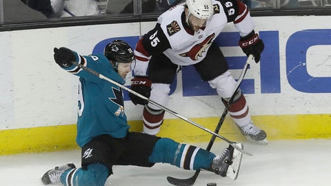 San Jose Sharks center Logan Couture, bottom, falls in front of Arizona Coyotes defenseman Jason Demers (55) during the third period of an NHL hockey game in San Jose, Calif., Tuesday, Feb. 13, 2018. (AP Photo/Jeff Chiu)