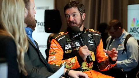 Martin Truex Jr., right, answers questions during an interview during media day for the NASCAR Daytona 500 auto race at Daytona International Speedway, Wednesday, Feb. 14, 2018, in Daytona Beach, Fla. (AP Photo/John Raoux)