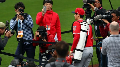 Los Angeles Angels' Shohei Ohtani takes the field past members of the media during a spring training baseball practice on Wednesday, Feb. 14, 2018, in Tempe, Ariz. (AP Photo/Ben Margot)