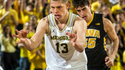 Michigan forward Moritz Wagner (13) reacts after making a three point basket, followed by Iowa forward Luka Garza (55), in the first half of an NCAA college basketball game at Crisler Center in Ann Arbor, Mich., Wednesday, Feb. 14, 2018. (AP Photo/Tony Ding)