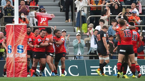 FILE - In this April 23, 2016, file photo, players of Japan's Sunwolves celebrate their 36-28 win over Argentina's Jaguares, in black, during their Super Rugby match in Tokyo. The 2018 Super Rugby season will test the concept that less is more, demonstrating whether a tournament pared back from 18 to 15 teams will become stronger to win back jaded fans. The Sunwolves and the Jaguares survived the cull of three teams, though both have under-performed since joining the tournament in 2015 when Super Rugby expanded from 15 to 18 teams. (AP Photo/Koji Sasahara, File)
