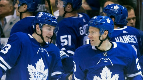 Toronto Maple Leafs' Dominic Moore, right, celebrates with Travis Dermott after scoring his team's opening goal against Columbus Blue Jackets during the first period of an NHL hockey game, Wednesday, Feb. 14, 2018 in Toronto. (Chris Young/The Canadian Press via AP)