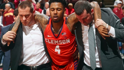 Clemson guard Shelton Mitchell, center, is helped off the court after being injured in overtime of the team's NCAA college basketball game against Florida State on Wednesday, Feb. 14, 2018, in Tallahassee, Fla. Florida State won 81-79. (AP Photo/Phil Sears)