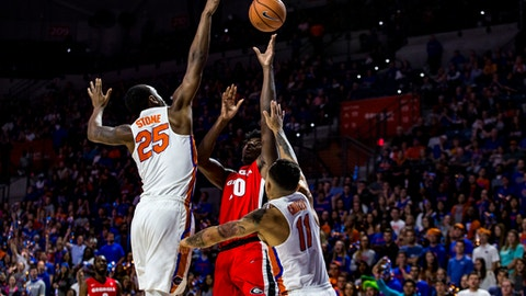 Florida forward Keith Stone (25) and guard Chris Chiozza (11) pressure Georgia guard Teshaun Hightower (10) during the first half of an NCAA college basketball game in Gainesville, Fla., Wednesday, Feb. 14, 2018. (Lauren Bacho/The Gainesville Sun via AP)