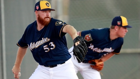 Milwaukee Brewers starting pitchers Brandon Woodruff (53) and Chase Anderson throw during a drill at the team's spring training baseball facility Thursday, Feb. 15, 2018, in Maryvale, Ariz. (AP Photo/Carlos Osorio)