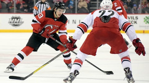 New Jersey Devils center Nico Hischier (13) looks to pass the puck as Carolina Hurricanes defenseman Brett Pesce (22) defends during the second period of an NHL hockey game Thursday, Feb. 15, 2018, in Newark, N.J. (AP Photo/Bill Kostroun)