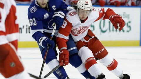 Tampa Bay Lightning center Steven Stamkos (91) and Detroit Red Wings left wing Tyler Bertuzzi (59) collide while chasing the puck during the second period of an NHL hockey game Thursday, Feb. 15, 2018, in Tampa, Fla. (AP Photo/Chris O'Meara)
