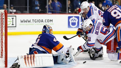 New York Islanders goaltender Jaroslav Halak (41), of Slovakia, fends off New York Rangers center David Desharnais (51) and Rangers right wing Jesper Fast (17) as New York Islanders center John Tavares (91) gets in the middle on a play that was ruled not a goal during the third period of an NHL hockey game in New York, Thursday, Feb. 15, 2018. (AP Photo/Kathy Willens)