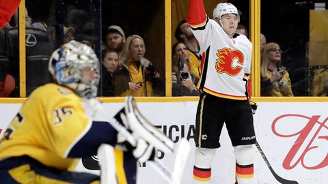 Calgary Flames center Curtis Lazar, right, celebrates after scoring a goal against Nashville Predators goalie Pekka Rinne (35), of Finland, in the third period of an NHL hockey game Thursday, Feb. 15, 2018, in Nashville, Tenn. (AP Photo/Mark Humphrey)