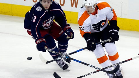 Philadelphia Flyers forward Dale Weise, right, passes the puck past Columbus Blue Jackets defenseman Zach Werenski during the third period of an NHL hockey game in Columbus, Ohio, Friday, Feb. 16, 2018. The Flyers won 2-1 in overtime. (AP Photo/Paul Vernon)