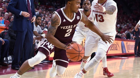 Texas A&M guard TJ Starks tries to get past Arkansas defender Dustin Thomas during the first half of an NCAA college basketball game Saturday, Feb. 17, 2018, in Fayetteville, Ark. (AP Photo/Michael Woods)