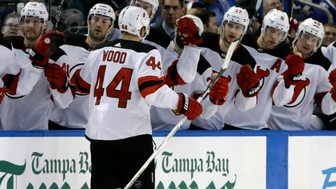 New Jersey Devils left wing Miles Wood (44) celebrates with teammates on the bench after scoring against the Tampa Bay Lightning during the third period of an NHL hockey game Saturday, Feb. 17, 2018, in Tampa, Fla. The Devils won 4-3. (AP Photo/Chris O'Meara)