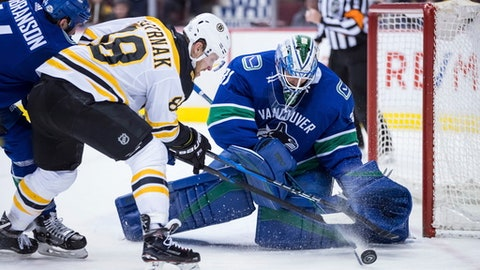 Boston Bruins' David Pastrnak, of the Czech Republic, is stopped by Vancouver Canucks goalie Anders Nilsson, right, of Sweden, as Erik Gudbranson, back left, defends during the first period of an NHL hockey game Saturday, Feb. 17, 2018, in Vancouver, British Columbia. (Darryl Dyck/The Canadian Press via AP)