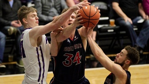 Saint Mary's center Jock Landale, center, reaches for a rebound along with Saint Mary's guard Jordan Ford, right, and Portland forward Joseph Smoyer during the first half of an NCAA college basketball game in Portland, Ore., Saturday, Feb. 17, 2018. (AP Photo/Steve Dipaola)