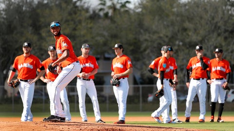 Miami Marlins pitcher Sandy Alcantara stands on the mound as teammates wait their turn during a drill during spring training baseball practice Sunday, Feb. 18, 2018, in Jupiter, Fla. (AP Photo/Jeff Roberson)