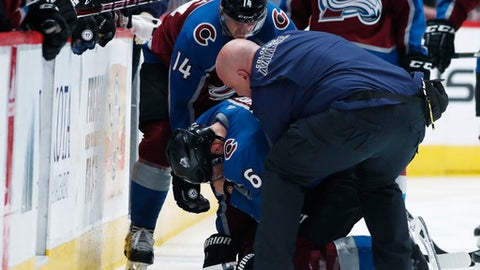 Colorado Avalanche head athletic trainer Matthew Sokolowski, front, picks up injured defenseman Erik Johnson, center, with the help of left wing Blake Comeau in the third period of an NHL hockey game against the Edmonton Oilers, Sunday, Feb. 18, 2018, in Denver. The Oilers won 4-2 to break a six-game losing streak. (AP Photo/David Zalubowski)