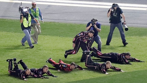 Austin Dillon, center, celebrates with his crew as they dive on the grass in the infield after winning the NASCAR Daytona 500 auto race at Daytona International Speedway, Sunday, Feb. 18, 2018, in Daytona Beach, Fla. (AP Photo/John Raoux)