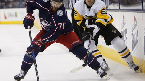 Columbus Blue Jackets' Nick Foligno, left, carries the puck across the blue line as Pittsburgh Penguins' Carl Hagelin, of Sweden, defends during the second period of an NHL hockey game Sunday, Feb. 18, 2018, in Columbus, Ohio. (AP Photo/Jay LaPrete)