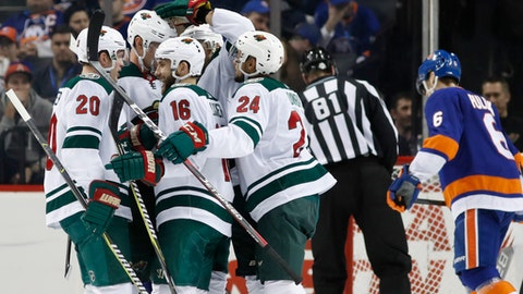 Minnesota Wild teammates celebrate with Wild left wing Jason Zucker (16) after he scored a goal on New York Islanders goaltender Jaroslav Halak during the second period of an NHL hockey game in New York, Monday, Feb. 19, 2018. (AP Photo/Kathy Willens)