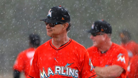 Miami Marlins manager Don Mattingly walks through a steady rain during spring training baseball practice Monday, Feb. 19, 2018, in Jupiter, Fla. (AP Photo/Jeff Roberson)