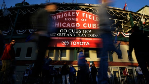FILE - In this Oct. 18, 2017 file photo, fans arrive at Wrigley Field before Game 4 of baseball's National League Championship Series between the Chicago Cubs and the Los Angeles Dodgers in Chicago. Wrigley Field will still feel plenty familiar to Cubs fans this season even as the 104-year-old ballpark undergoes more major renovations. Cubs owner Tom Ricketts, optimistic about chasing the teams second World Series title in three seasons, visited his teams spring training home Monday, Feb. 19, 2018 for the first full-squad workout by the 2016 World Series champions on a cool day in the desert. (AP Photo/Nam Y. Huh)