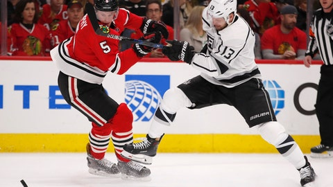 Los Angeles Kings left wing Kyle Clifford (13) battles for control of the puck with Chicago Blackhawks defenseman Connor Murphy (5) during the first period of an NHL hockey game Monday, Feb. 19, 2018, in Chicago. (AP Photo/Jeff Haynes)
