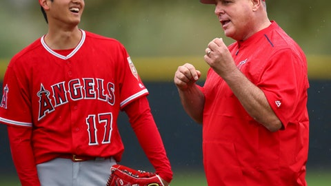 FILE - In this Feb. 14, 2018, file photo, Los Angeles Angels' Shohei Ohtani, left, smiles while listening to manager Mike Scioscia during a spring training baseball practice in Tempe, Ariz. Scioscia says the spring training game plan for Ohtani is still being mapped out. On Tuesday, Feb. 20, Scioscia, said Ohtani will throw a bullpen session on Thursday and a decision will be made after that on when the multi-talented Japanese pitcher/hitter will make his first appearance in a spring training game. (AP Photo/Ben Margot, File)