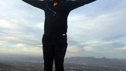 In this photo from Thursday, Feb. 15, 2018, San Francisco Giants pitcher Johnny Cueto stands atop Camelback Mountain in Scottsdale, Ariz. In each of his three springs with San Francisco, Cueto has picked a rental home nearby Camelback, on a different side of the idyllic landmark every year to be close by his favorite hiking terrain. (AP Photo/Janie McCauley)
