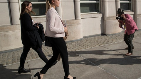 Tennis star Eugenie Bouchard, second from left, is photographed as she leaves Brooklyn Federal court with her mother, Wednesday, Feb. 21, 2018, in New York. Bouchard testified during her negligence lawsuit against the United States Tennis Association that a wet floor caused her to slip and fall inside a locker room at the 2015 U.S. Open. (AP Photo/Mary Altaffer)