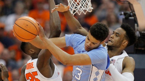 North Carolina's Cameron Johnson, center, grabs a rebound from Syracuse's Bourama Sidibe, left, and Syracuse's Oshae Brissett, right, during the first half of an NCAA college basketball game in Syracuse, N.Y., Wednesday, Feb. 21, 2018. (AP Photo/Nick Lisi)
