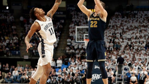 Michigan's Duncan Robinson (22) knocks down a three pointer as Penn State's Lamar Stevens (11) defends during the first half of an NCAA college basketball game in State College, Pa., Wednesday, Feb. 21, 2018. (AP Photo/Chris Knight)
