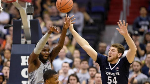 Georgetown center Jessie Govan, back left, passes the ball against Xavier forward Sean O'Mara (54) and forward Naji Marshall, front left, during the second half of an NCAA college basketball game, Wednesday, Feb. 21, 2018, in Washington. Xavier won 89-77. (AP Photo/Nick Wass)