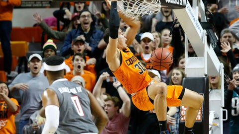 Oklahoma State guard Jeffrey Carroll dunks in front of Texas Tech forward Tommy Hamilton IV (0) during the second half of an NCAA college basketball game in Stillwater, Okla., Wednesday, Feb. 21, 2018. (AP Photo/Sue Ogrocki)