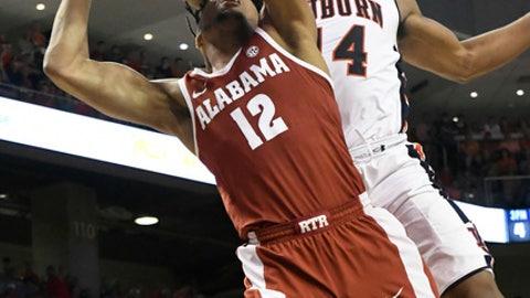 Auburn guard Malik Dunbar fouls Alabama guard Dazon Ingram (12) under the basket during the first half of an NCAA college basketball gameWednesday, Feb. 21, 2018, in Auburn, Ala. (AP Photo/John Amis)