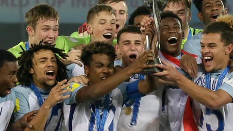 FILE - This is a Saturday, Oct. 28, 2017 file photo of England's soccer team as they celebrate with the trophy after winning the FIFA U-17 World Cup in Kolkata, India. England might to the first and last team to be holders of both the Under-20 and Under-17 World Cups. FIFA is looking to merge the youth tournaments won last year by England to create a 48-team competition, emulating the expansion of the main mens World Cup. Officials are exploring the merits of an age cut-off at 18 or 19. (AP Photo/Anupam Nath/File)