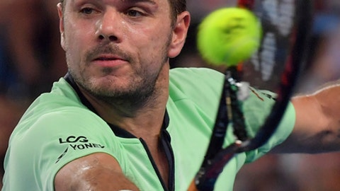 Switzerland's Stan Wawrinka hits a backhand return to United States' Tennys Sandgren during their second round match at the Australian Open tennis championships in Melbourne, Australia, Thursday, Jan. 18, 2018. (AP Photo/Andy Brownbill)