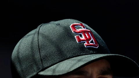Washington Nationals pitcher Tim Collins wears the cap of the Marjory Stoneman Douglas High School Eagles baseball team before the start of an exhibition spring training baseball game against the Houston Astros Friday, Feb. 23, 2018, in West Palm Beach, Fla. Players around the league are wearing the caps to remember the victims of a shooting at the school last week. (AP Photo/Jeff Roberson)
