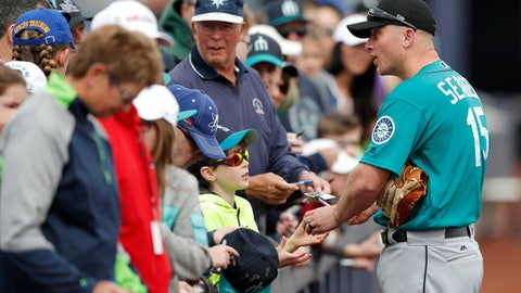 Seattle Mariners third baseman Kyle Seager, right, gives autographs to fans before a baseball spring exhibition game against the San Diego Padres, Friday, Feb. 23, 2018, in Peoria, Ariz. (AP Photo/Charlie Neibergall)